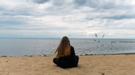 Back view of a woman at the Gulf of Finland, Saint Petersburg, Russia. Concept. Rear view of a young girl in black clothes with long hair sitting on a sandy beach and looking far away in the distance.