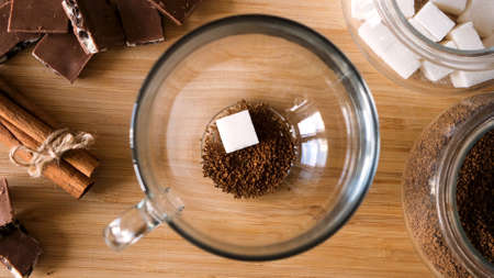 Top view of instant coffee preparation process. Concept. Putting coffee, sugar cube, and hot water into the transparent mug on wooden table background with chocolate and cinnamon.