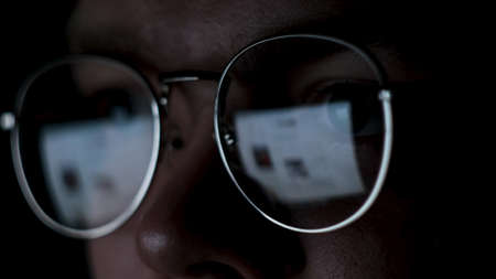 Man works on internet with the reflection of a monitor inside glasses. Concept. Close up of male face wearing glasses with the screen reflected in lenses isolated on black background.