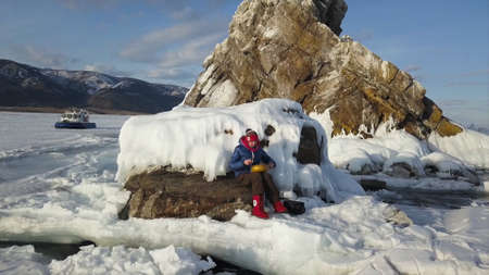 Aerial view of a woman playing steel tongue drum while sitting on a rock among snow and ice of a frozen lake. Clip. Meditation with tank drum and sticks.