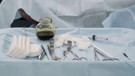 Surgical equipment set for surgery in operation room in the hospital. Action. Close up of medical tools, iodine cup and white cotton balls and sterile gauze, concept of medicine. 写真素材
