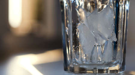 Throwing ice pieces into a transparent glass, preparing cocktail. Concept. Close up of crystal glass standing on the table filled with cold ice on blurred background. 写真素材
