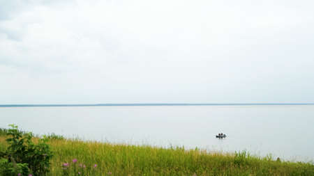 Green field and a calm lake with floating rubber boat. Concept. Fresh green grass and flowers on the shore of the big lake on cloudy sky background in the summertime. 写真素材