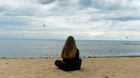 Young woman sitting on sea shore and looking into the distance. Concept. Rear view of young girl with long curly beautiful hair looking at flying seagulls, dramatic background.