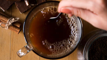 Close up of preparing hot beverage. Concept. Hand holding coffee spoon and stirring hot coffee on vintage old wooden background with cinnamon and chocolate.