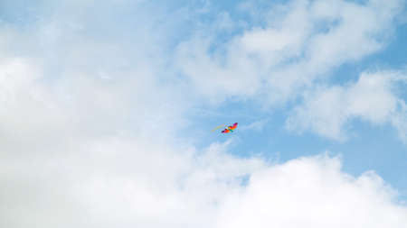 Kite flying in the sky among the clouds. Concept. Bottom view of the summer blue sky with white clouds and soaring rainbow colorful kite, concept of freedom and childhood.