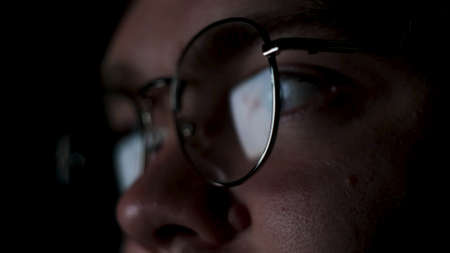 Glasses with reflected computer screen in lenses. Concept. Close up of thoughtful business man face or focused student working late at night isolated on black background. 写真素材