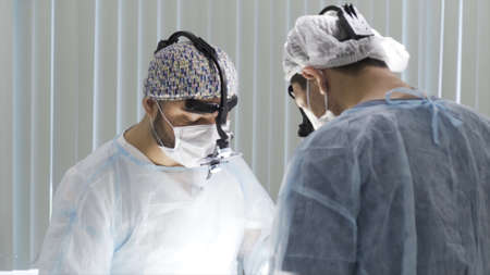 Two surgeons working at the operating clean room. Action. Two male doctors wearing sterile uniform and binocular loupe while performing surgery, concept of health care and medicine.