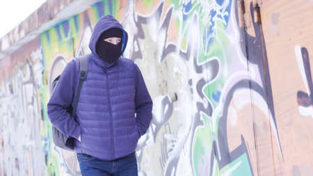 Serious young man in casual outfit and balaclava walking along the grafitti wall. Action. Male with a backpack hiding his face and looking around, concept of vandalism.