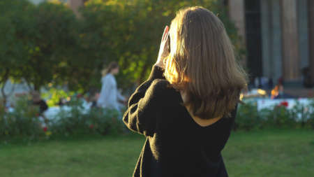 Rear view of woman in black sweater holding photocamera and taking photo at summer green park. Media. Young girl photographing sights in a big city in the summertime.
