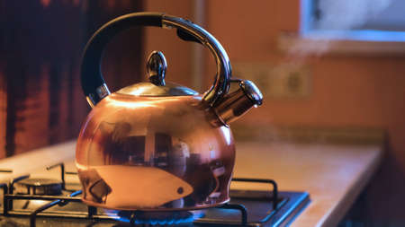 Close-up of silver teapot boiling on stove. Concept. Boiling kettle on stove in beautiful evening kitchen interior. Stream of steam comes out of kettle on stove