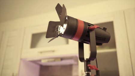 Modern LED spotlight for indoor lighting during photo or video shooting. Action. Close up of glowing illuminator indoors, concept of professional equipment.