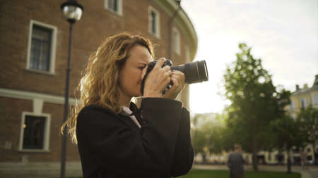 Woman takes photos with camera on background of old architecture and tourists. Action. Beautiful woman takes pictures of historical sights of city on professional camera in sunny weather