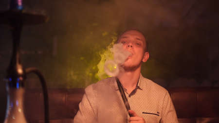 Portrait of man smoking traditional hookah pipe and making smoke clouds in a form of rings. Media. Man exhaling smoke in hookah cafe or lounge bar.
