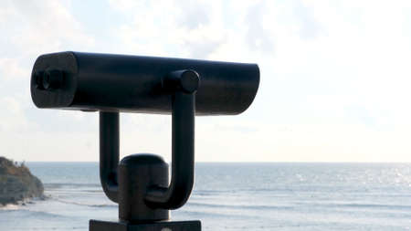 Public beach binoculars, operated with coins with the ocean in the background. Concept. Touristic binoculars, optical instrument for breathtaking views.