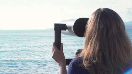Beautiful woman looking through binoculars on background of sea and mountains. Media. Young woman views seascape with mountains in pair of binoculars on sunny day