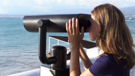 Happy girl enjoying marine view through binoscope. Media. Young woman uses coin operated binocular to observe landscape, ocean, beach, scenes at the coast.