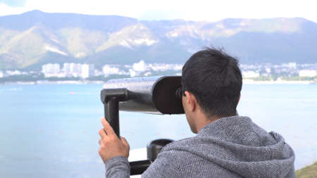 A man looking through coin binoculars on fantastic mountain and sea view. Media. Male tourist looks at the coastal city through coin binoculars.