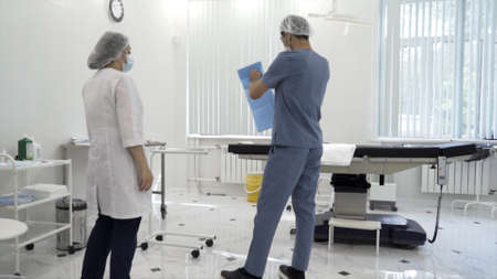 Male and female nurses preparing a sterile room for the surgical procedure. Action. Rear view of care workers in a surgical room before the procedure. Stockfoto
