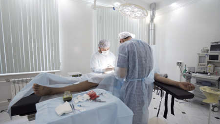 Gallbladder removal operation in the operation theatre. Action. Doctors helping patient during the surgery, bloody bandage is lying on the sterile table.