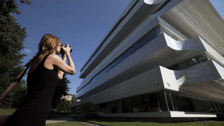 Woman photographer standing and photographing modern city building. Action. Female tourist holding camera and looking at unusual building on a sunny summer day.
