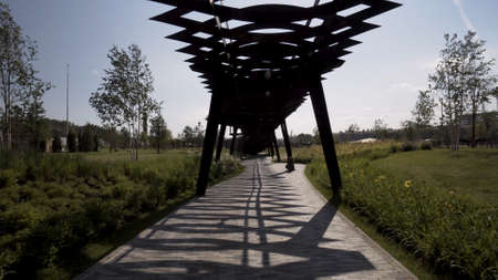 Walking under the unusual wooden construction of Tyufeleva roshcha park. Action. Tuffel grove park, modern public place located in Moscow, Russia. Stok Fotoğraf