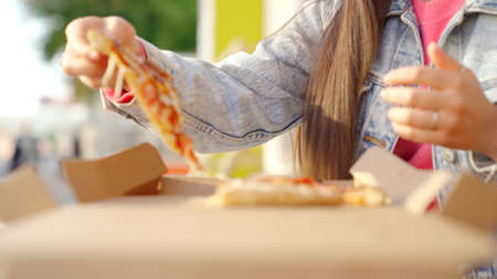 Italian food lunch, woman eating pizza with mozzarella outdoors. Media. Close up of young female hand taking a slice of pizza on a summer sunny day.