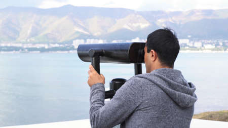 Man enjoying wonderful view. Media. Rear view of a young man traveler looking through binoculars with coins against the backdrop of the landscape with the sea and mountains. Banque d'images