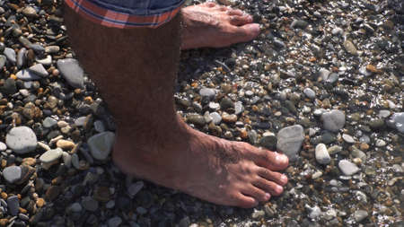 A sea waves on a stone beach covering the rocks and male feet. Media. Close up of man standing on the sea shore, summer rest and vacancy concept.