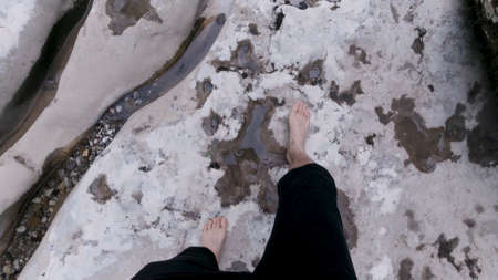 Man walking barefoot on giant stones in a clean mountain river. Clip. Travel concept, top view of male legs and feet walking through cold stream. Stok Fotoğraf