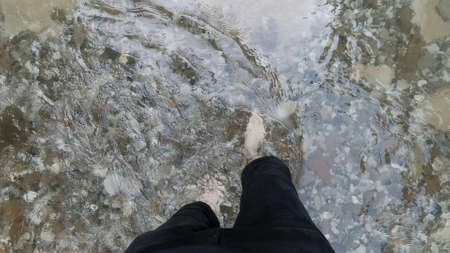 Man feet with hairy legs crossing cold mountain stream. Clip. Top view of male bare legs walking through cold river with stony bottom, concept of hiking. Stok Fotoğraf