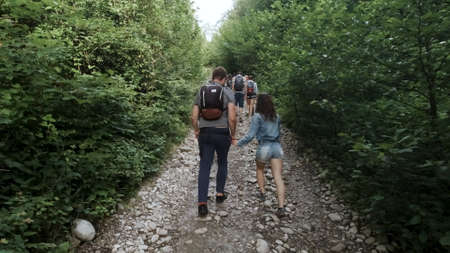 Man with backpack and woman hikers trekking in forest. Clip. Rear view of young couple walking with a group of travelers on a stony trail along the trees and bushes.