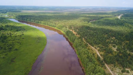 Aerial view of the river and green forest under blue sky in the summer. Clip. Summer landscape with forest, green fields and wide river on a sunny day.