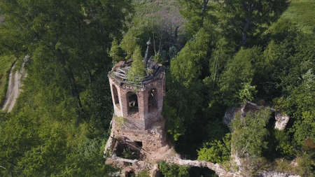 Beautiful details of an abandoned church left in summer forest on a sunny day. Clip. Aerial view of Ivy growth on building ruins among green trees.