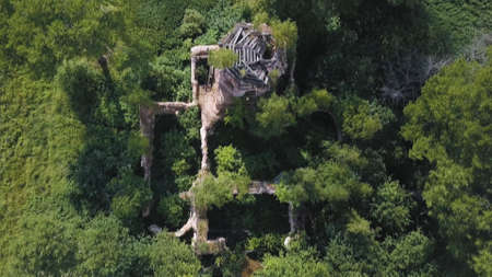 Aerial view of lush forest on a sunny summer day and an old church. Clip. Flying over ruins of the ancient stony church located among green trees.