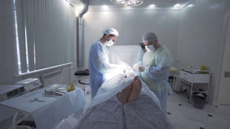 Surgeons team working with the patient who is awake in surgical operating room. Action. Two men doctors performing surgical operation on male genitals.