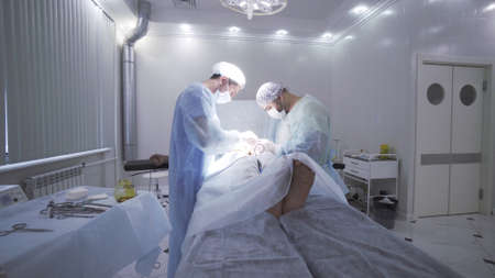 Surgeons team working with the patient who is awake in surgical operating room. Action. Two men doctors performing surgical operation on male genitals. Stok Fotoğraf