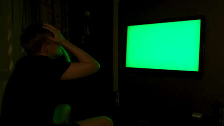 Side view of an emotional man watching TV with green screen at home at night. Concept. Man looking stressed and disappointed while watching sports game on TV with chroma key.