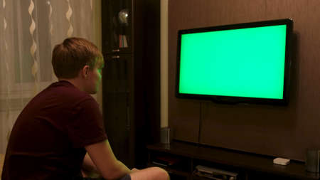 Man sitting on the couch in the living room and watching TV with green screen. Concept. Side view of young man turning off TV with chroma key and walking away. Stok Fotoğraf