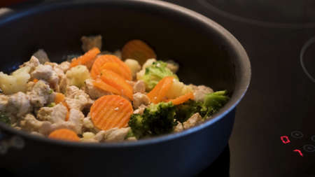 Cooking chicken with vegetables in a black frying pan standing on a touch sensitive hob. Concept. Preparing healthy dinner, frying carrots, broccoli, and cauliflower with white chicken meat. 免版税图像