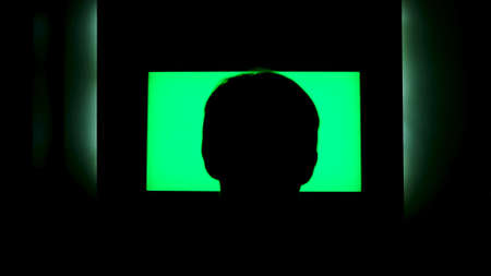 Rear view of a male head silhouette in front of tv with green screen. Concept. Man watching TV with chromakey that hanging on the wll at night at home.
