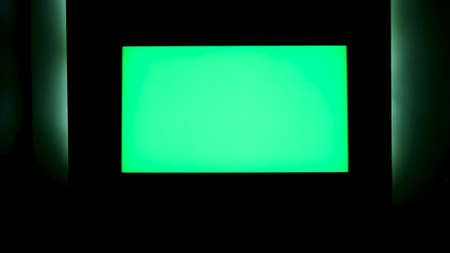 TV with horizontal green screen on a black wall with green illumination. Concept. Close up of chroma key TV screen in a dark room at night.