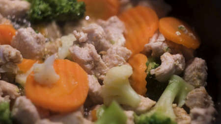 Close up of vegetables in a pan being prepared with white chicken meat. Concept. Cooking tasty dinner of carrots, broccoli, cauliflower, and chicken pieces.
