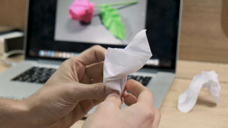 Male hands making origami figure from white paper. Stock footage. Man fails to make a flower from paper like on a picture on a computer screen,