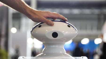 Close up of male hand touching a head of a robot at the exhibition. Media. Man patting on the head of a moving plastic humanoid robot, concept of modern technologies.