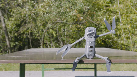 Drone is sitting on table. Action. Funny figure from drone sitting on table in Park. Robotic drone sits and amusingly waves part. Sculpture of friendly robot from drone