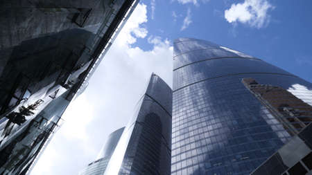 Bottom view of glass skyscrapers on background blue sky. Action. Dizzying view of business high-rise in center of modern city. Glass skyscrapers reflect blue sky