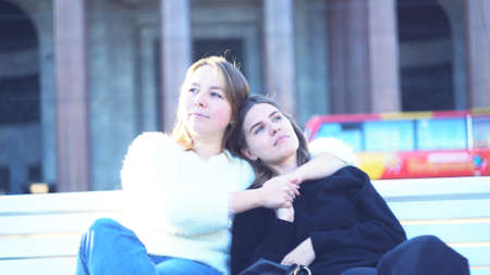 Girlfriends sitting on park bench enjoying each other, concept of LGBT. Media. To female lesbians sitting on a white bench in front of an old building with granite pillars.