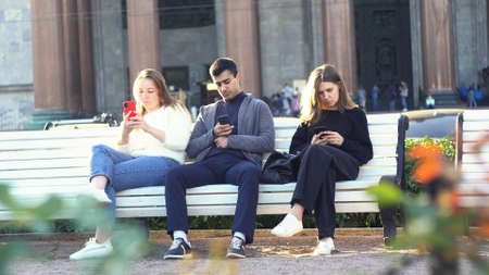 Concept of smartphone addiction. Media. Group of friends, one man and two women sitting outdoor on a bench in park and watching something on mobile phones.