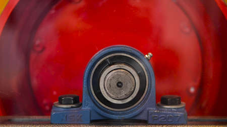 Close-up of rotating red cylinder. Media. Rotating industrial drum is red in color. Large screws with rotating industrial cylinder